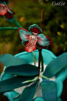 """Polymer clay orchid in a glass """"pot"""" #polymerclay #orchid #flower #turquoise #red #white #dots"""