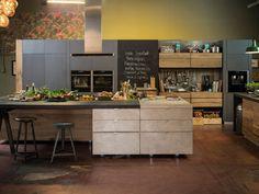 Gastküche mit Insel, Tresen, Stauraum. Wandtafel und hochgelegten E-Geräten