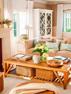 Salón con mesa de centro de madera, sofá gris, vitrina blanca y cestas de fibra natural
