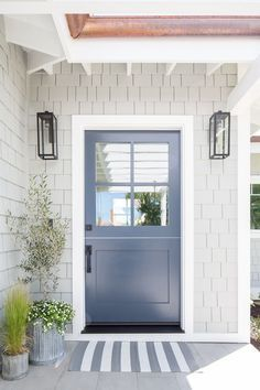 Gray beach home features a blue front door with windows styled with a striped do.Gray beach home features a blue front door with windows styled with a striped doormat, galvanized planters and gray shingles illuminated Exterior Paint Colors For House, Paint Colors For Home, Gray Exterior Houses, Cottage Exterior Colors, Beach Cottage Exterior, Dutch Door Exterior, Exterior Paint Ideas, Stucco Exterior, Coastal Cottage