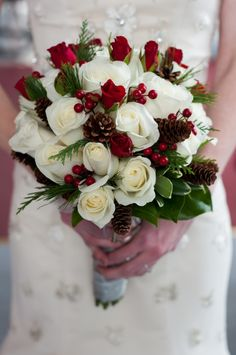 bridal bouquet with red and white roses, pinecones, and holly berries