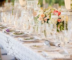 Tall, glass floating candle holders surround low floral arrangements for a fresh afternoon feel.