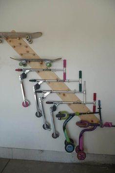 Idée d'un rangement utile en bois sur mur uni blanc. Multitude de skates et de trottinettes de différentes couleurs, allant du rose au vert.