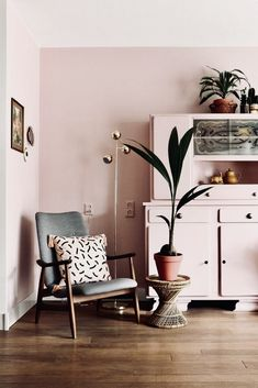 Pink scandi living room with grey mid-century chair and plants