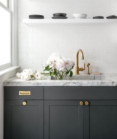 Dark gray kitchen cabinets accented with aged brass knobs, vintage brass inset pulls, and a honed gray and white marble countertop completed with a marble sink and aged brass gooseneck faucet fixed beneath stacked white floating shelves mounted on all white subway backsplash tiles.