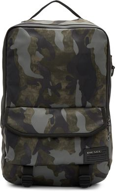 Textile backpack featuring camouflage pattern in tones of green and grey. Carry handle at top. Adjustable padded shoulder straps with cinch fastening. Compartment featuring Velcro foldover flap and elasticized fastening at face. Faux-leather logo patch in black at face. Cinch straps at base. Mesh panel at back face. Two-way zip closure at main compartment. Zippered pocket, patch pocket, and 13