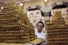 A salesman promotes the traditional Syrian sweet food in the Abou Arab Haider sweet shop at the midan street of Damascus, June 23, 2010. Syrian people are fond of sweet food in their daily life and the local products are popular among the overseas tourists