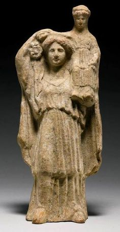 Demeter standing with Persephone sitting on Her left shoulder and clasping Her daughter's arm, and wearing a chiton with double overfold, and himation -at Sotheby's, London