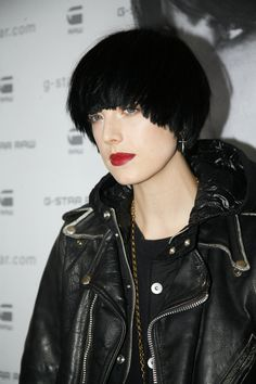 Jet black hair color stands out against her very fair complexion. Her red lips are another strong contrast.  The cut is short and somewhat boyish. There is no part. All the strands are directed from the top of the crown and are very straight with blunt edges. The bangs are full and come down over the eyebrows. Black leather completes her look. More on Agyness Deyn Bowl Cut