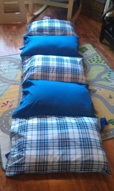 DIY nap pad. Or in my case get the grandmothers to DIY. Five pillow cases sewn together with old pillows. Added ribbon to keep with storage.