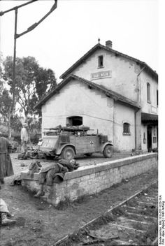 A view of British wounded and German soldiers at the northeast end of the station of Sidi-Nsir. A Kubelwagen ambulance has arrived and one stretcher has been loaded. The name of the station, Sidi Nsir, is visible on the station sign. Tunisia ,1943.
