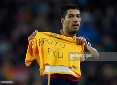 Barcelona's Uruguayan forward Luis Suarez displays a jersey reading 'I support PKU' as he celebrates after scoring during the Spanish league football...