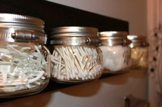 DIY mason jar bathroom organizer. Piece of wood, metal straps, small mason jars. Mount to wall. Fill jars with flossers, cotton swabs, cotton balls, etc. Perfect for a modern or industrial type decor..