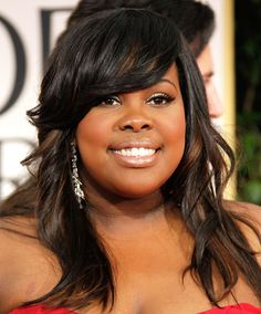 Amber Riley: Round Amber Riley's side-swept bangs get an extra boost of volume from a deep side part. By swooping gently over one eye, they create a feminine and flattering shape that helps lengthen her face. A side swept bang draws the eye diagonally instead of vertically, making this a flattering choice for square faces as well
