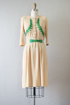 Vintage late 1930s yellow crepe rayon dress, long sleeves, padded shoulders, and vivid green leather  leaves appliqued on the front bodice. Skirt has soft pleats from the waist that helps define the figure. Dress has matching belt.