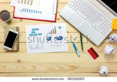 Top view business  discussing charts and graphs with laptop and credit card, notebook, flower on office desk