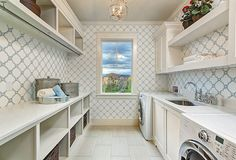 Laundry room. Galley style laundry room with blue quatrefoil wallpaper. Do you like having the laundry machines separate? It's not very practical in my opinion, but I love everything else.  Clark and Co Homes.