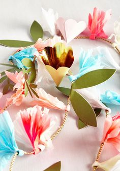 You may not have grown the pretty paper flowers on this garland yourself, but you still deserve credit for the charming choice to decorate with 'em! Strung on a metallic gold rope, pastel peach, neon pink, sky blue, and white blooms 'n' fronds bring terrace appeal to your sweet space.