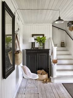 Black furniture and frames add simple contrast to this Swedish cottage entry with light pine floors and white beadboard  walls and ceiling.