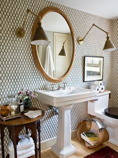 Lights (arm wall scones) and wallpaper are amazing in this eclectic-yet-classic bathroom.