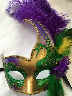Purple, green and gold Mardi Gras Mask with purple, green and yellow feather and ribbon ties.