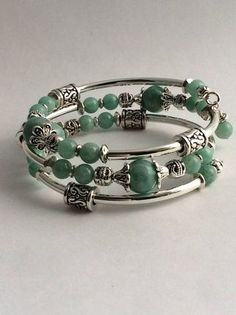 This wrap bracelet is made with silverplated memory wire and consists of 2 sizes of Amazonite gemstone beads and a variety of silver-tone and pewter spacer beads. A charm and bead dangle complete the bracelet ends. A memory wire bracelet is the perfect gift for yourself or someone special since it does not require sizing. The bracelet adjusts to most size wrists and does not have a clasp, making it very easy to put on and take off. Click here to see other wrap bracelets in my shop…