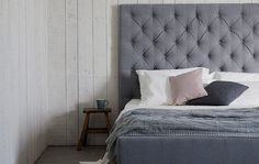 Homes - From Dawn to Dusk: bed with pink and grey cushions on grey wall