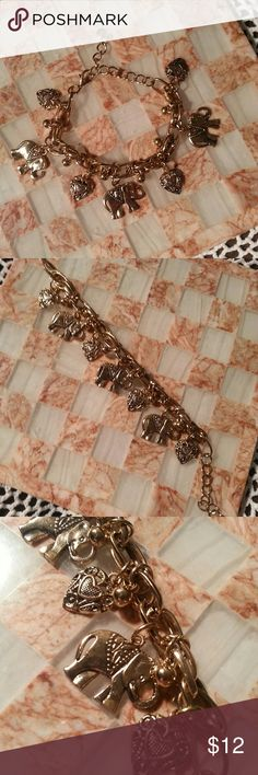 Charm bracelet Gold tone charm bracelet with three elephant charms and for heart charms. Measures 7 in from large metal Loop to end claw clasp. Measurement does not include Shane dangling for clasp. na Jewelry Bracelets