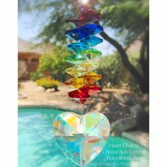 Heart Chakra Crystal Rainbow Suncatcher ♥ To activate good ch'i (energy) and to help bring in new opportunities and abundance, hang a crystal sun catcher in a window near your front door. ♥ RobynNola.com