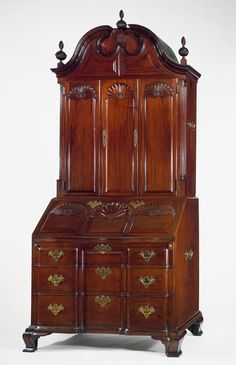 The most original American furniture was made in Newport, Rhode Island by the Townsend and Goddard families. The shell motif is a characteristic of Newport furniture, and here the blocking on the lower drawers continues upward to the bookcase