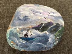 This brave person is sailing on the ocean waters, with the deep colorful mountains, sky and birds surrounding him. Its a beautiful day!  I hand paint all of my stones with acrylic and then finished with matte finish varnish to protect the paintings without the harsh glare of gloss. So, no need to worry about water or spills.  Makes a beautiful and unique gift, or just keep for yourself...inside to enjoy or outside in your garden.  This unique rock measures 4 W x 3.5 H and also comes in a…