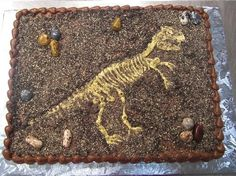 1. cover cake in chocolate icing 2. pipe skeleton 3. shake cookie crumbs to almost cover (Animal crackers and Oreo crumbs mixed). The party was at the Science Center's Dino display