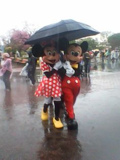 Mickey and Minnie sharing an umbrella in the rain