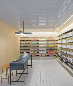 The shop is entered through a dark area described by Tuckey as a felt-lined tunnel. Beyond it, the simple space features illuminated wood-panel walls, whitewashed floorboards and a reflective ceiling. Shop Interior Design, Retail Design, Interior Ideas, Wood Panel Walls, Wood Paneling, Visual Merchandising, Bath And Beyond Coupon, Retail Shop, Uk Retail