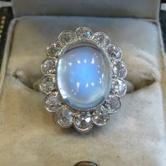 This ring is the ultimate show-stopper! A fabulous dinner ring or a completely unique engagement ring.  The ring is from the mid-1800's, including the original center stone a 3.4ct moonstone. The ring of diamonds around the moonstone are all mine cut diamonds and equal 1ct total weight. The setting is platinum and the shank is a 14k white gold.  As with all antiques, each piece is completely unique, please contact us to check for availability.