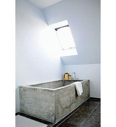 Contra o piso escuro e as paredes brancas, a banheira de cimento queimado se destaca neste ambiente