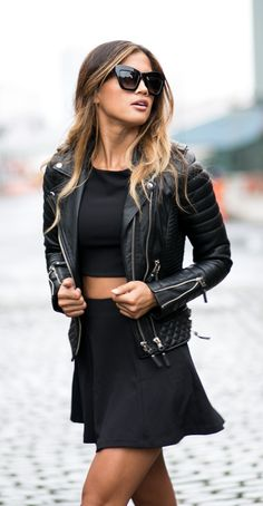 Rocky Barnes is wearing a black skirt and crop top from Sam and Lavi, leather jacket from Boda Skins, and the sunglasses are from Valley Eyewear