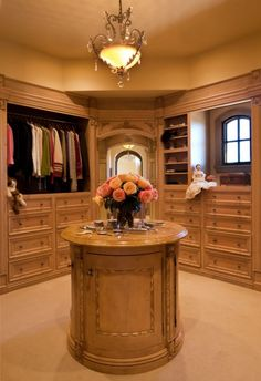 feminine dressing room with tiny arched window, round island, drawers galore & great architectural detail