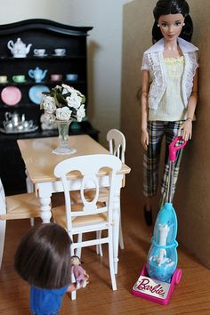 """Barbie - Trying to finish her housework so she can enjoy a day of shopping at Penny Lane boutique tomorrow, Elizabeth vacuums while daughter, Tulley, follows her around with her """"Boo"""" doll."""
