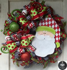 This is a Christmas wreath made with deco mesh. It features colors of red, black, lime green and white. It has a handpainted Santa clause with harlequin hat, red and lime green ornaments and picks and matching bows. 24H x 24W  See more items http://www.etsy.com/shop/mrschristmasworkshop