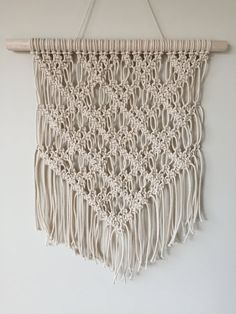 Macramé Wall Hanging made with 100% cotton cord. It measures 32cm at its widest point, is 46cm long and is hanging on a 40.5cm dowel stick. It includes a 25mm gold ring at the top, ready for you to hang. This one of a kind piece is perfect for any living area, bedroom, workspace or anywhere youd like fill an empty space or bring some texture and art to your walls. If you would like a similar piece made or a custom order, please dont hesitate to reach out to me. Check out other Wall…