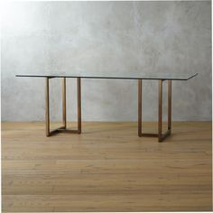 """shine and dine.  A gilded update to our popular chrome version.  Two sleek brass """"sawhorses"""" partner with crisp, clear glass tops, rectangle or round—your choice.  For more leg room and stability, turn the brass-plated iron structures T-in at the ends (shown). 2-piece brass-plated iron base with levelers1/2""""-thick clear glass topClean top with a glass cleaner, dust base with a soft, dry clothMade in Taiwan."""