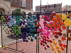Crocheted flowers are showing up on the fencing erected around the Tower Building in Elgin. | Janelle Walker~For Sun-Times Media