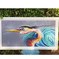 This one of a kind is bursting with abundant color . The Heron is a beloved bird here in Florida, where we are sure to see on just about every waterway. Popping color against a slate grey. This guy has his feathers frisky and flowing! Made to order