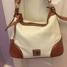 Dooney&Bourke ivory bag Leather shoulder bag with two pockets inside ..key holder .. Beautiful  hardware Has two small ink marks showing on the photo .. Great bag .. Great condition .. Stain can be remove  not that noticeable .. Comes with dust bag . Dooney & Bourke Bags Shoulder Bags