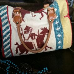 Navajo Print Carpet Bag  W/  Leather Handles. Cute bag! Pretty colors, cream white, red, turquoise, golden yellow, and brown. Excellent condition except one pen mark inside purse as shown in pic. Measures 10 inches X  8 inches. Bags Satchels
