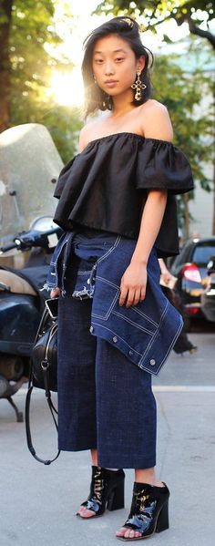 Margaret Zhang wears an off the shoulder blouse, denim culottes and black patent mules paired with gold earrings and a shoulder-length haircut