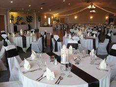 White Table Linens with Black Satin Table Runner, White Chair Covers & Black Satin Sash, and White Napkins