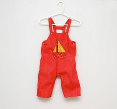 Vintage red overalls with sailboat applique.