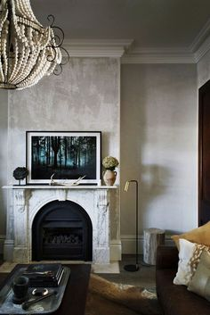 Living room with a glamorous chandelier and a marbled mantle